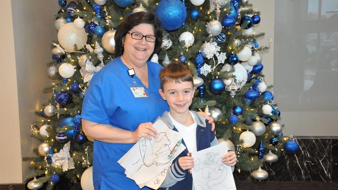 Vassar Brothers Medical Center child life worker Theresa Palome and Tyler Costa hold some of the busy books donated by children from Marlboro Elementary School.