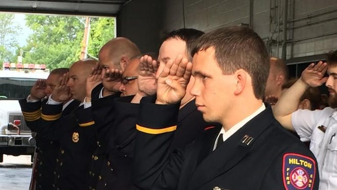 Emergency responders salute during a 9/11 event at the Ridge Road Fire District.