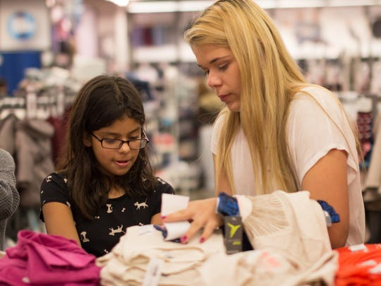 Adonica Mendoza, 17, of Las Cruces looks at shirts with Daniela Villado, 11, during a recent Dress the Child shopping event at Old Navy, Two more Dress the Child shopping dates are slated Nov. 22 and Dec. 6.