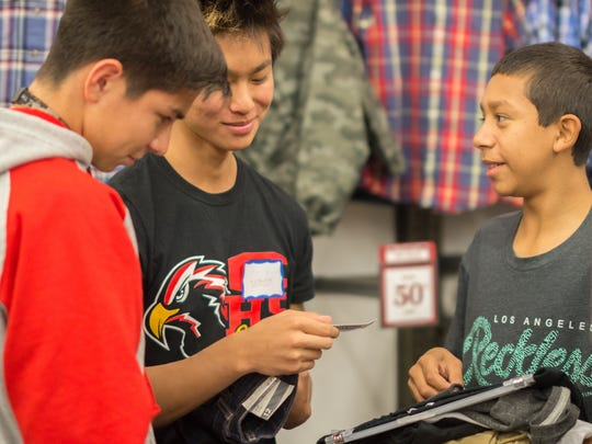 Andrew Angel, 15, of Las Cruces, left, Kento Nakano, middle, help Anthony Orta find the right size pair of jeans during a Dress the Child on Nov. 8 at Old Navy, 2200 E. Lohman Ave.