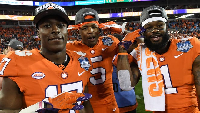 Clemson wide receiver Cornell Powell (17), left, wide receiver Tee Higgins (5), and wide receiver Trevion Thompson celebrates after the team beat Miami 38-3 for the ACC football championship in Charlotte on Saturday.
