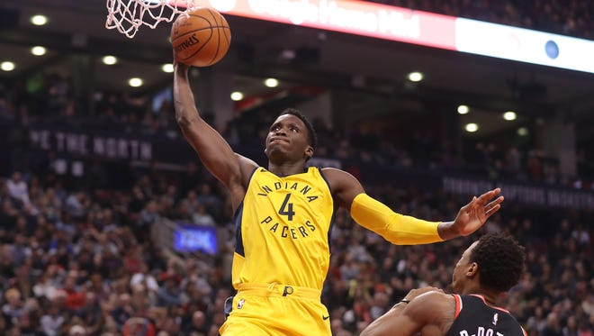 Indiana Pacers guard Victor Oladipo (4) drives past Toronto Raptors guard DeMar DeRozan (10) as he goes up to dunk the ball at Air Canada Centre.