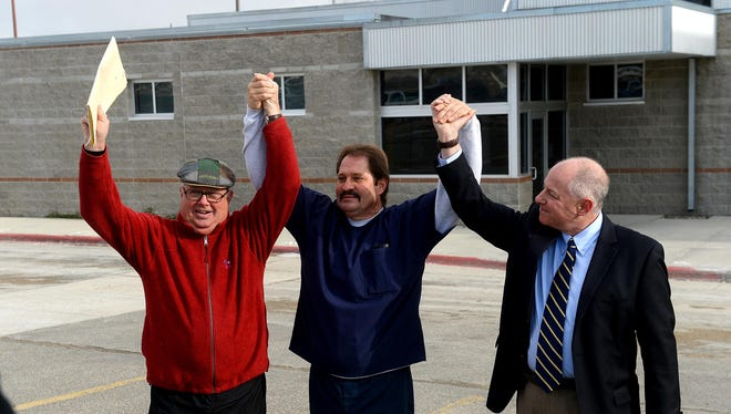 Barry Beach, center, flanked by Jim McCloskey of Centurion Ministries, left, and attorney Peter Camiel, raise their arms in victory Nov. 20 as Beach is released from Montana State Prison in Deer Lodge.