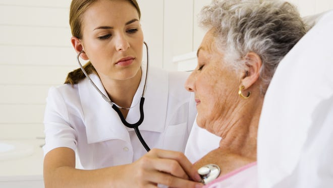 Nurse checking woman's heartbeat.