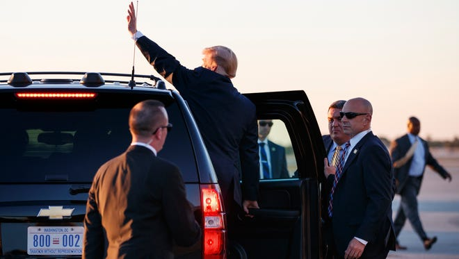 President Donald Trump waves from his motorcade vehicle to people cheering him across the tarmac as he arrives on Air Force One at Palm Beach International Airport, in West Palm Beach, Fla., March 23 with first lady Melania Trump and their son Barron Trump.