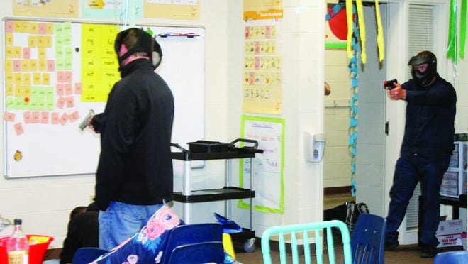 An armed staff member intervenes in a school shooting scenario in a classroom in Magazine Saturday afternoon. Several district staff members underwent 60 hours of training to become commissioned school security officers last week.
