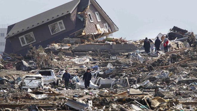 People walk in the rubble in Minamisanriku town, Miyagi Prefecture, northern Japan, Sunday, March 13, 2011, two days after a powerful 9.0 earthquake-triggered tsunami hit the country's east coast.