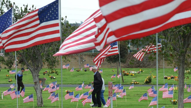 People visit gravesites at the Ivy Lawn Memorial Park  andFuneral Home.  in Ventura on Veterans Day 2014.