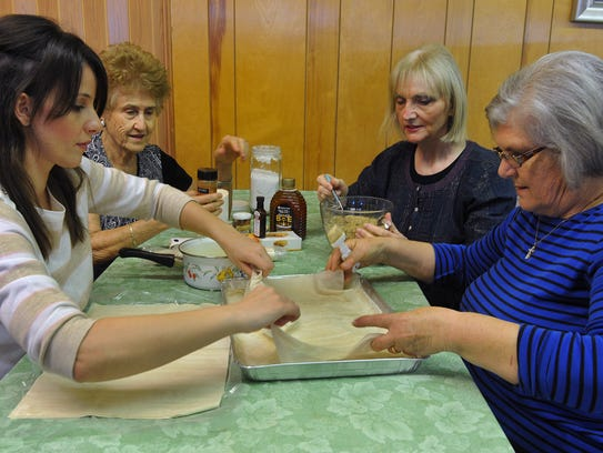 In this file photo, Rania Panagiotopoulos, left, Anthe Atalis, Eleni Moshtaghi and Flora Ataliotis, right, make pastries in preparation for this weekend's Greek Bake Sale at the Holy Cross Greek Orthodox Church.