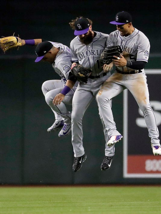 From left to right, Colorado Rockies' Gerardo Parra, Charlie Blackmon and Carlos Gonzalez celebrate after a baseball game against the Arizona Diamondbacks, Saturday, March 31, 2018, in Phoenix. (AP Photo/Matt York)