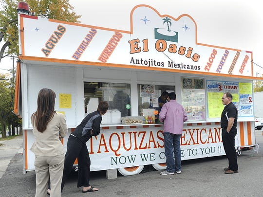 Customers line up to order food at the El Oasis food stand located on Michigan Avenue in Lansing, Oct. 2, 2012.