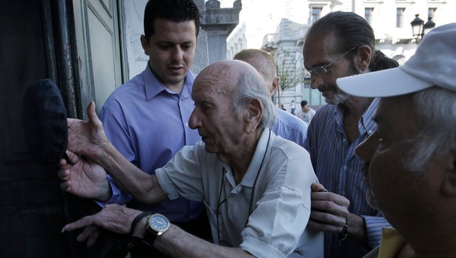 A retiree is helped by a bank employee as he enters a bank to get part of his pension in central Athens, Greece, 9 July 2015.