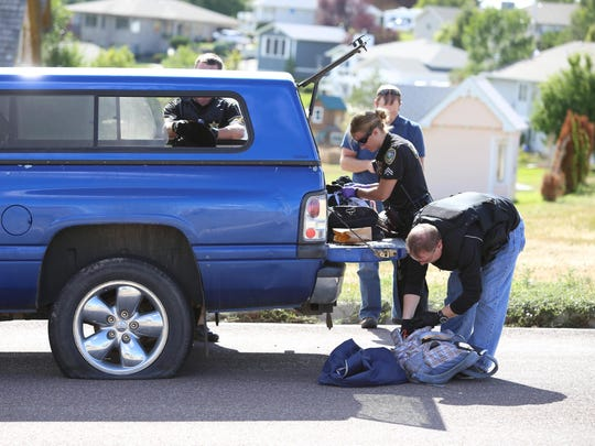 Law-enforcement officers search a vehicle in the Skyline