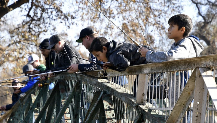 Fisherman gather on a bridge at Mooney Grove Park on