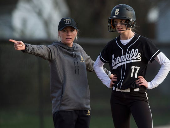 Boonville coach Alex Baumgart talks with the Pioneers' Madison Hill (17) at third base.