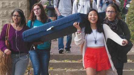 Students (including Zoë Dobkin back left) carry a mattress at a Carry That Weight event in October 2014 to promote sexual assault awareness.