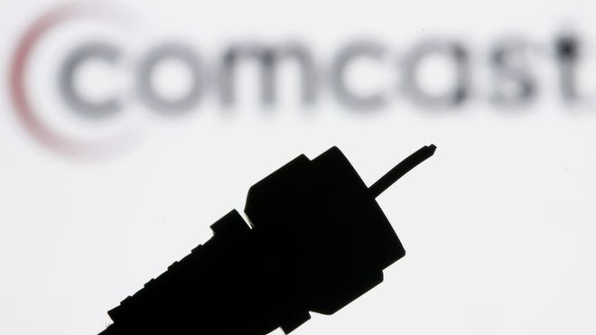 A silhouetted coaxial cable with the Comcast logo in the background.