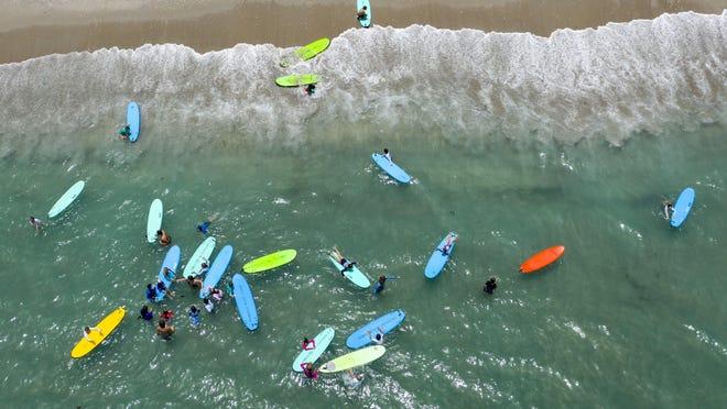 Kids enjoy the ocean during the Blue Water School of Surfing Summer Camp on June 29, 2020, in Jupiter, Florida.
