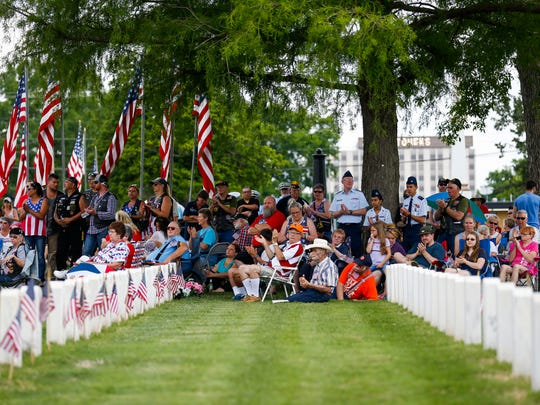 Veterans, their family members, and others huddle in the shade of trees to stay cool during a Memorial Day ceremony at the Springfield National Cemetery on Monday, May 28, 2018.