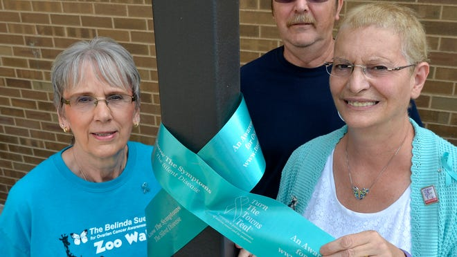 Sandy Corrigan and Michael and Margaret Kapolnek with one of the teal ribbons.
