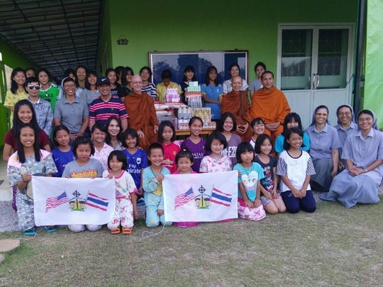Students, staff, Buddhist monks and Catholic nuns pose with Thailand Little Ones banners and a batch of supplies. Thailand Little Ones was started by Springfield restaurant owner Tong Trithara in 2015 to aid children in poverty in Thailand.