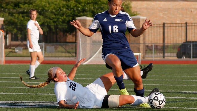 Lansing Christian's Abby Krueger, left, and University Liggett's Alexis Wenger battle for the ball during their MHSAA semifinal game Tuesday, June 14, 2016, at Troy Athens High School.