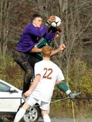 Ithaca goalie Brian Conuel jumps to take the ball off the head of Yorktown's Besim Bucpapa as Kevin Burgess (22) watches the play Saturday in a Class AA boys soccer state quarterfinal in Oneonta. Ithaca won, 2-1 and will play in the state final four this weekend at Middletown.