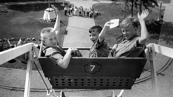 About 2,000 Register and Tribune carrier salesmen were treated to a day at Riverview Park in 1964 and rides at the amusement park were operating at capacity by 10 a.m. On ferris wheel are (from left) Randy Hartwig, 11, and Douglas Denton, 9, both of Marshalltown, and Joe McChurch, 13, of 6155 S.E. Fifth st. Carriers arrived at park on 40 chartered buses. Each carrier who produced five or more new orders on his route was eligible to attend.