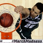 Michigan State's Travis Trice (20) dunks against Virginia on March 22. Michigan State won, 60-54, to advance to the Sweet 16 round of the NCAA Tournament.
