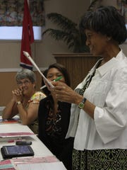 Karen Codjoe, right, reads the number of excess words the speakers used during their speeches at a recent Daybreak Toastmasters meeting.