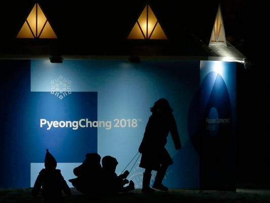 Children are pulled on a bobsleigh, in front of the 2018 Winter Olympics sign, in Pyeongchang, South Korea, Tuesday, Feb. 6, 2018. (AP Photo/Aaron Favila)
