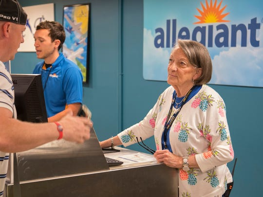 Helena Redmon, an agent with Allegiant Air, helps a customer moments before boarding a flight to Orlando, Fla., at the Owensboro-Daviess County Regional Airport Friday afternoon.