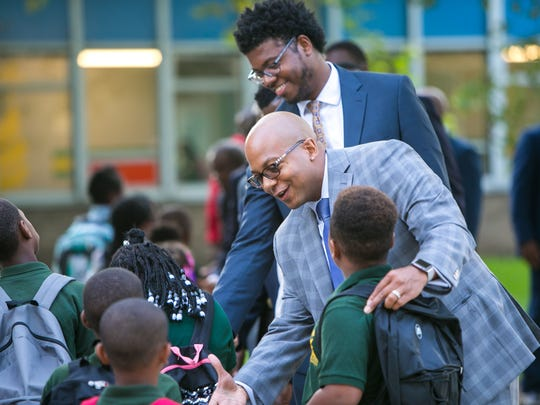 CEO of Eastside Charter School, Aaron Bass, (front) joins Atnre Alleyne and other black men in suits for Suit Up. Show Up., where over 25 African-American men stepped up to model what success looks like by welcoming students at EastSide Charter School on their first day of school.