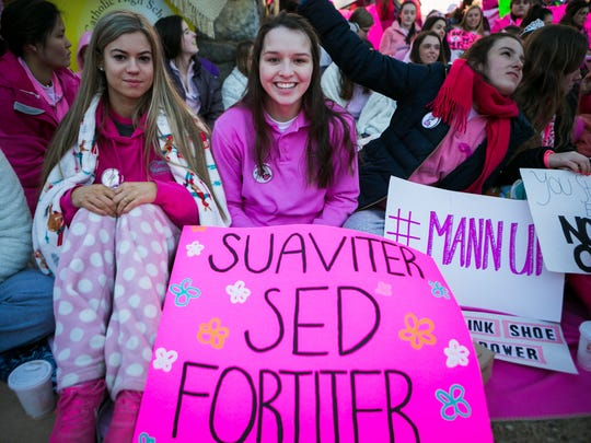 Vanessa Bartholomew (from left), Olivia Gruskiewicz holds a sign in Latin that says 'softly but strongly' and Amanda Patterson join their classmates at the steps of Padua Academy wearing pink in support of Cindy Mann, the head of Padua Academy, who was abruptly fired Friday.