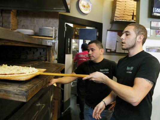 Sons of Sicily Pizzeria & Grill co-owner Joe Ferranti, left, holds the oven door open as cousin and co-owner Nick Falcone slides in a cheese pizza during lunch hour on Friday, March 14.
