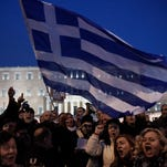 Pro-government protesters wave Greek flags in front of Greece's parliament to support the newly elected government's push for a better deal on Greeceís debt, in central Athens. Greece and the International Monetary Fund are in talks about Greece's ability to make upcoming payments on its bailout loans.