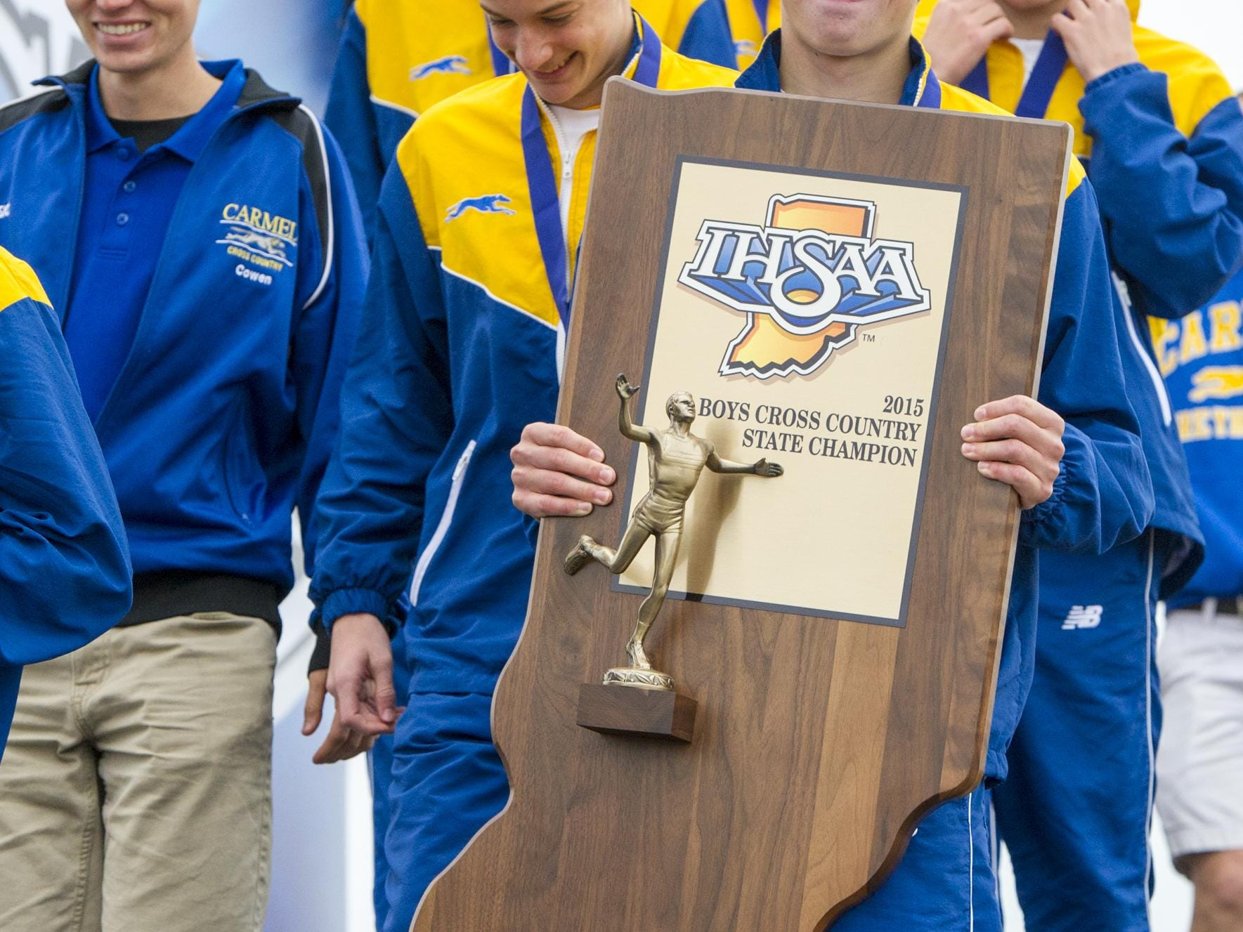 Carmel High School senior Ben Veatch (64) carries the championship trophy off the stage after the awards of the IHSAA Cross Country State Championship race at LaVern Gibson Championship Cross Country Course in Terre Haute, Ind. Saturday, Oct. 31, 2015. Carmel teams won both the boys and the girls titles.