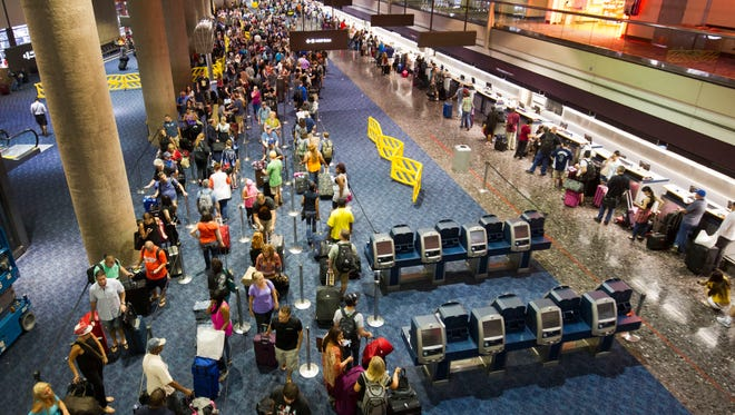 Departing Southwest Airlines passengers wait in line at Las Vegas' McCarran International Airport on Sunday, Oct. 11, 2015.