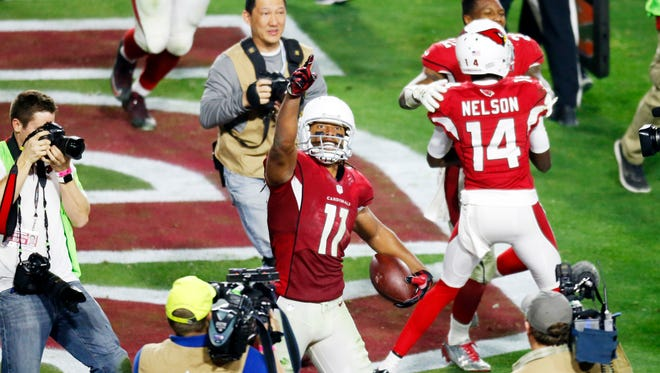 Cardinals receiver Larry Fitzgerald celebrates the game-winning touchdown against the Packers in overtime during the NFC Divisional playoff game at University of Phoenix Stadium in Glendale on Saturday, January 16, 2015.