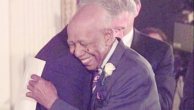 President Bill Clinton is embraced by Herman Shaw at a 1997 ceremony at the White House, where Clinton apologized on behalf of the government for the infamous Tuskegee Syphilis Study.