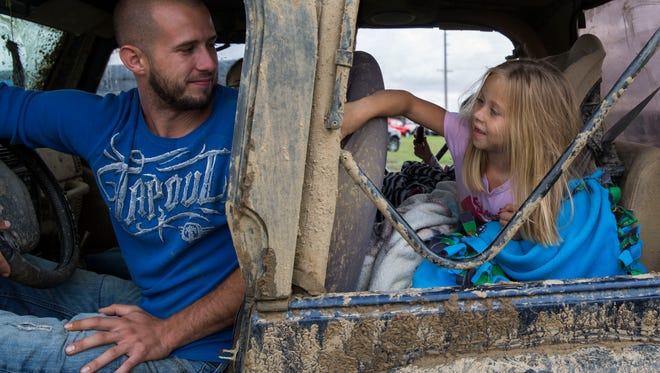 Keith Briody talks with his daughter Kaydence, 6, about how muddy their Jeep is as they show it off at the Jeep Jubilee on Saturday afternoon.