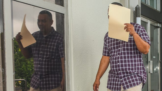 Joseph B. Cruz Jr. attempts to cover his face with a folder as he exits the District Court of Guam building in Hagåtña on Jan. 11, 2017. Cruz was sentenced to one year probation by the court for attempting to bribe a Guam Customs and Quarantine Agency officer.