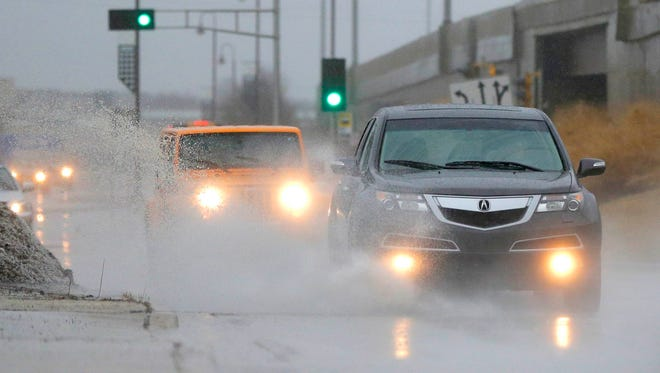 Vehicles travel through standing water on a street in Glendale, Wis., Tuesday, Feb. 20, 2018. A storm system stretched from Texas to the Great Lakes states and forced some schools to close. The National Weather Service issued winter weather advisories for parts of Oklahoma, Kansas, North Dakota, Missouri, Iowa, Minnesota and Wisconsin. Flood warnings were in effect in Illinois, Indiana and Michigan with flood watches in Texas and Arkansas.