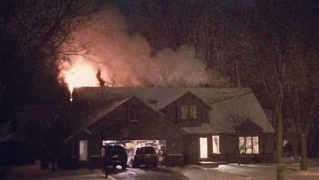 Smoke rises from the rear of a home on Pheasant Court in Appleton on Sunday night.