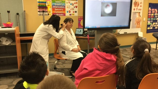 (L-R) Miho Yoshida, DO and Claire Galin, DO, demonstrate  imaging equipment that shows a patient's eardrum. The osteopaths demonstrated the medical equipment at University Hills Elementary's Career Day May 6.