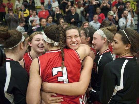 Members of the Ocean City girls' basketball team celebrate their 58-57 win over Ewing in the state Group 3 girls basketball semifinal game played at Deptford High School on Thursday.