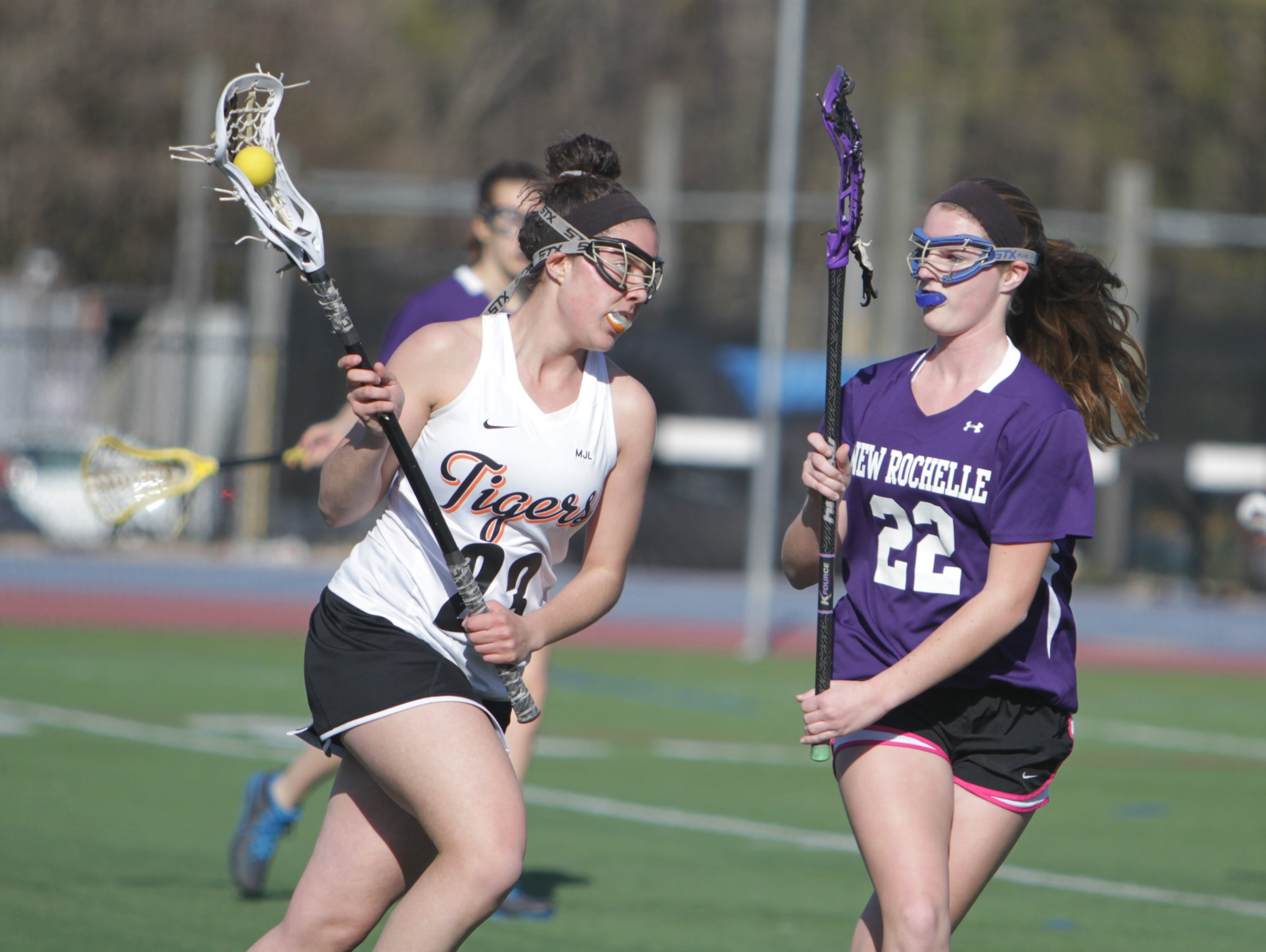 White Plains' Kali Peeples attempts to run past New Rochelle's Kelsey Freeman during a Section 1 girls lacrosse game between New Rochelle and White Plains at White Plains High School on Wednesday, April 13th, 2016. White Plains won 11-6.