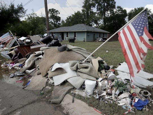 Tattered flags fly over a pile of water-soaked items as people clean up in a flood ravaged neighborhood Thursday in Houston.