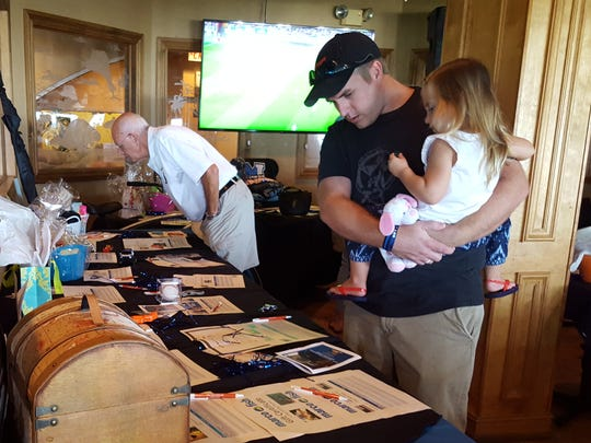 Members of the community browse silent auction items on Oct. 8 at Sunset Grille. The auction was part of the Marco Island Police Department's fundraiser for Mark Haueter, an officer diagnosed with cancer.