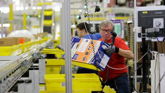 Mark Oldenburg processes outgoing orders at Amazon.com's fulfillment center in DuPont, Washington, on Nov. 30.